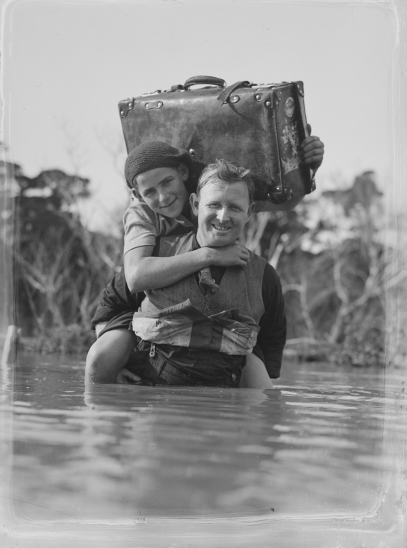 A_man_carries_a_child_across_a_body_of_water_(AM_87661-1)